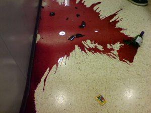 smashed bottle of red wine n supermarket aisle